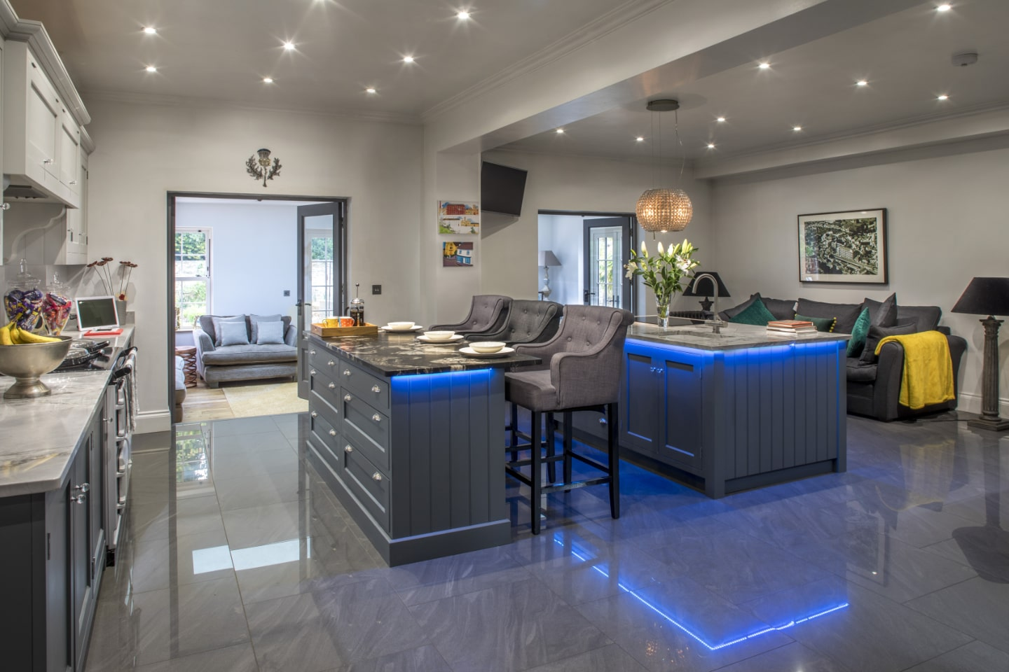 A bespoke kitchen with breakfast bar and blue LED lighting underneath.