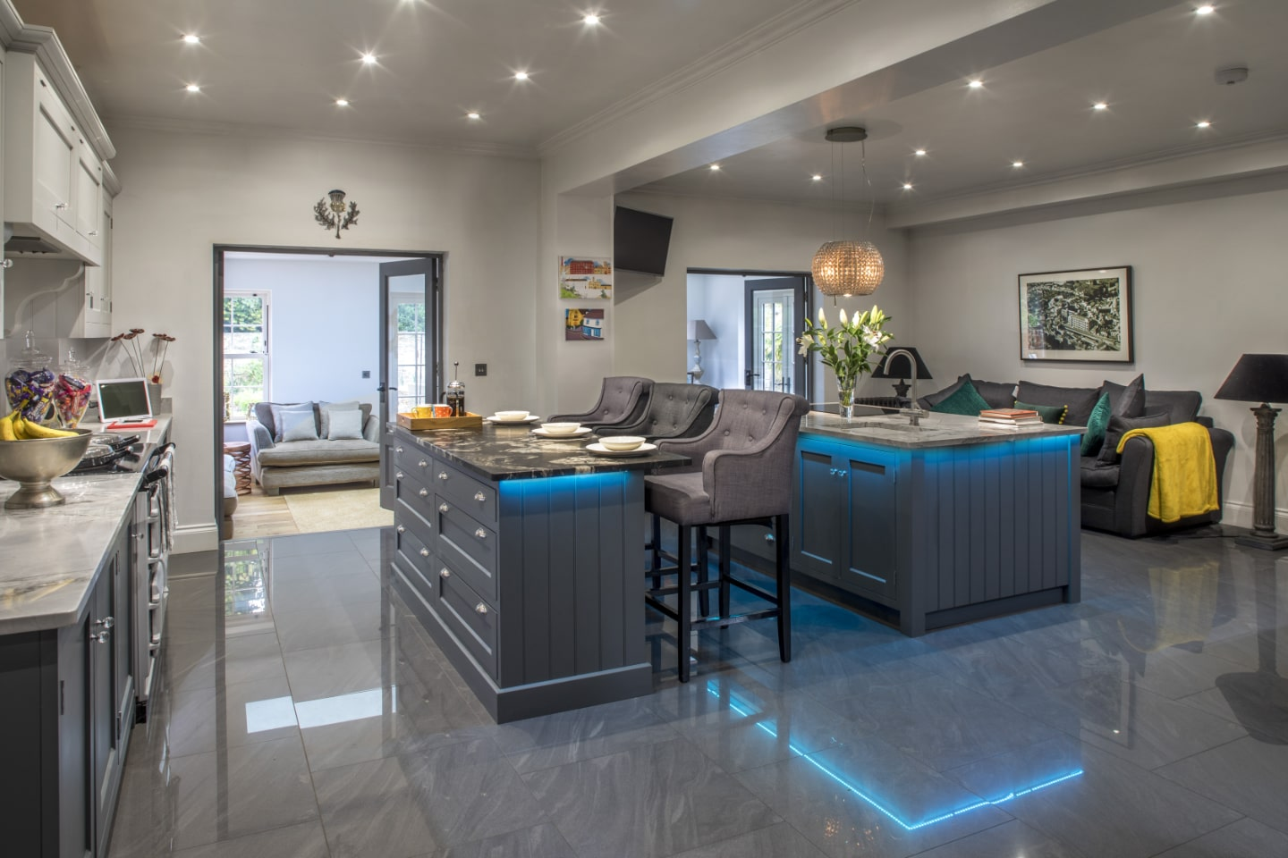 A bespoke kitchen with breakfast bar and turquoise LED lighting underneath.
