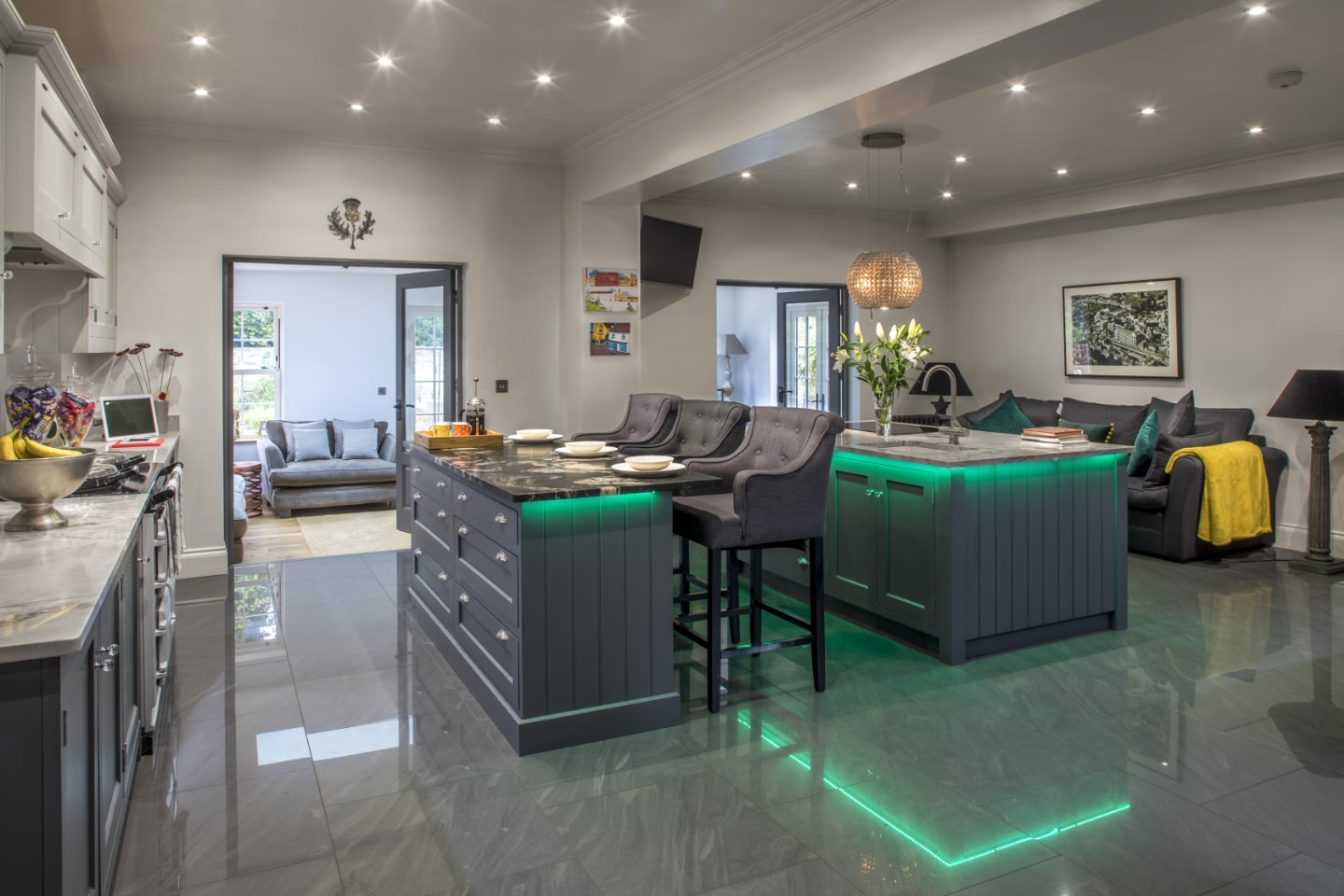 A bespoke kitchen with breakfast bar and green LED lighting underneath.