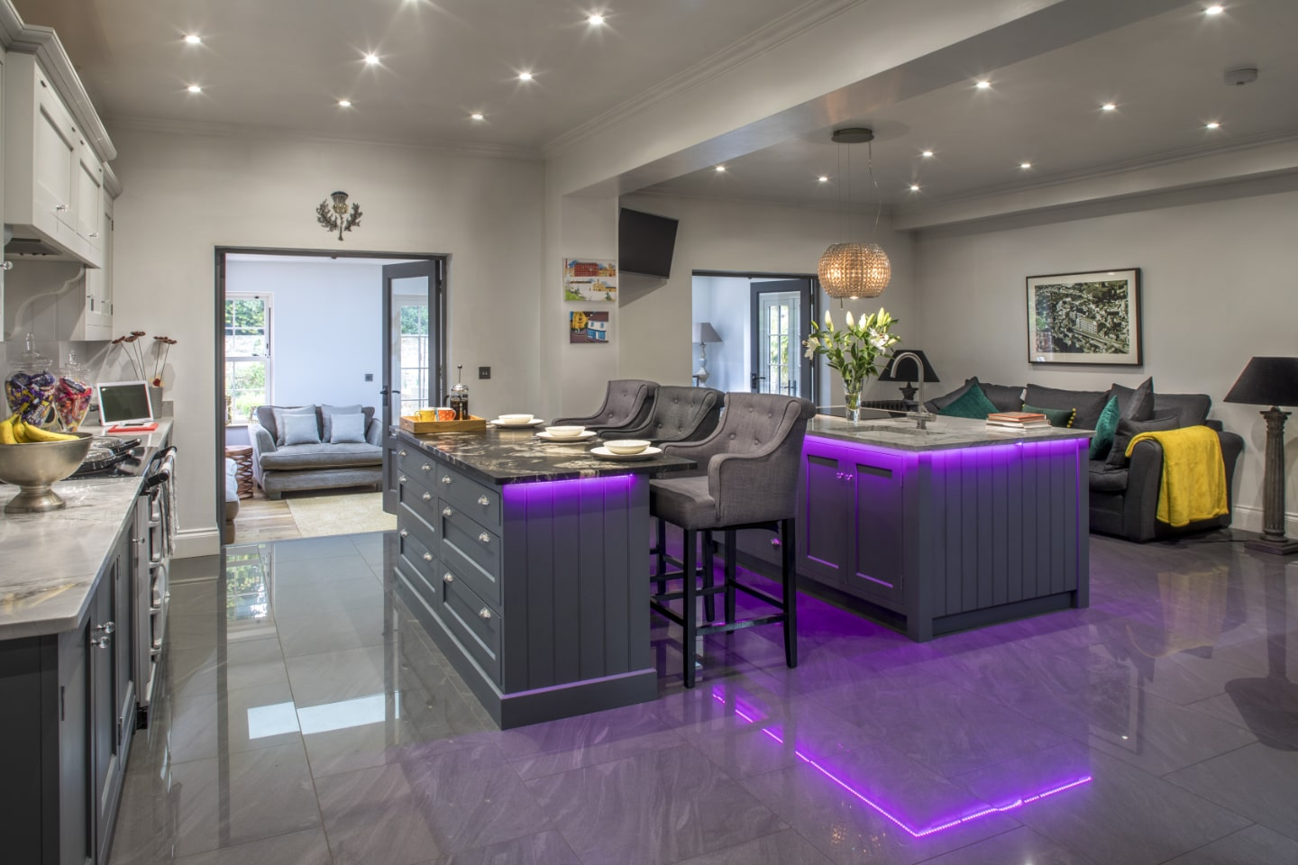A bespoke kitchen with breakfast bar and purple LED lighting underneath.