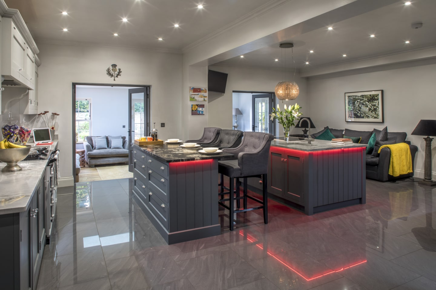 A bespoke kitchen with breakfast bar and red LED lighting underneath.