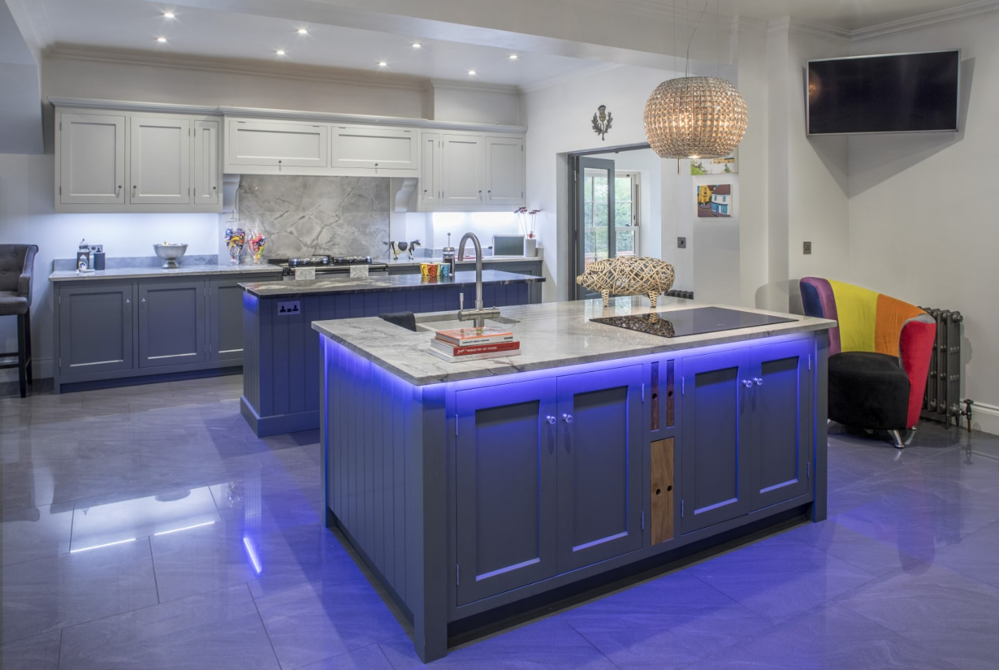 A bespoke kitchen with custom, blue LED lighting under the work tops.