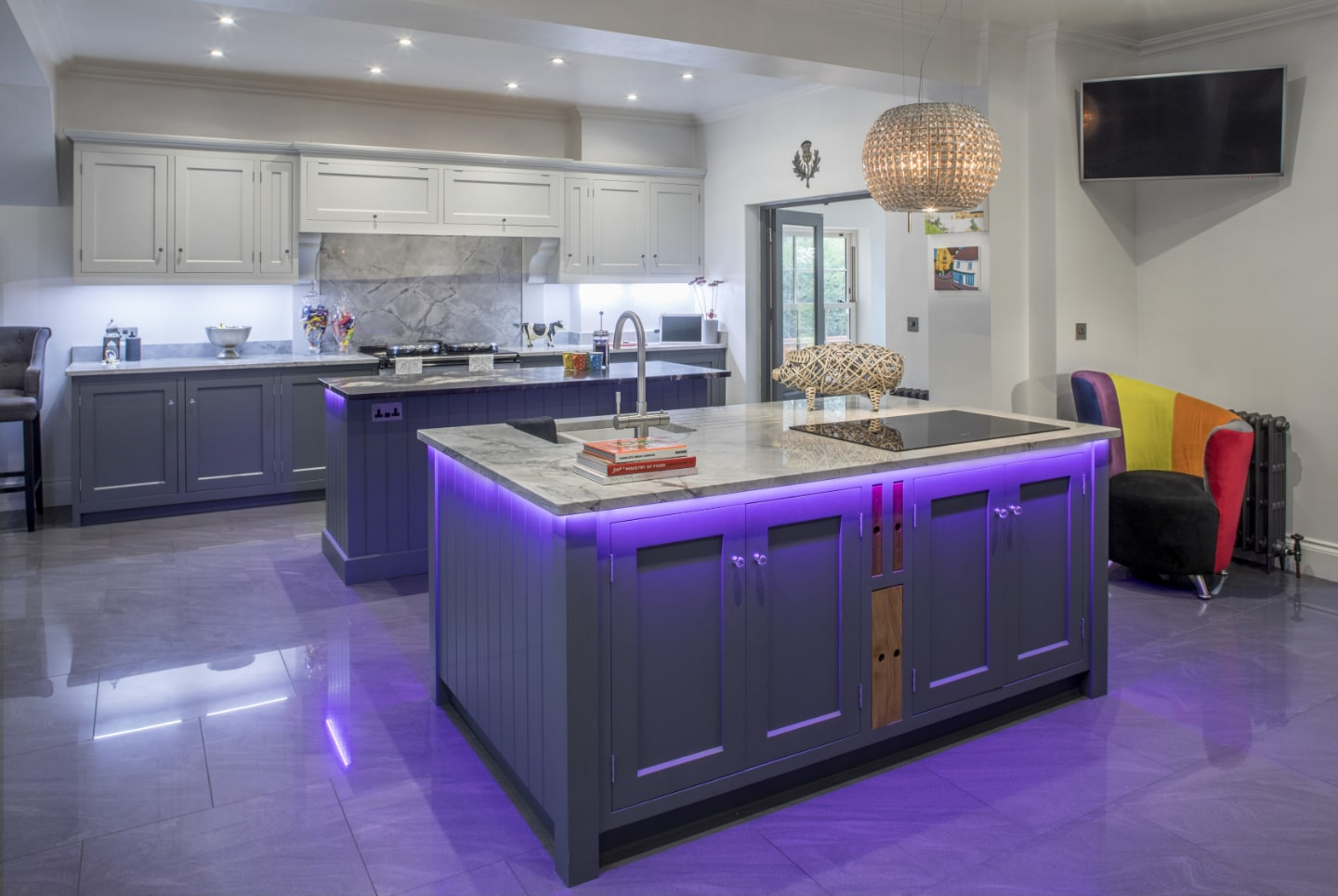 A bespoke kitchen with custom, purple LED lighting under the work tops.