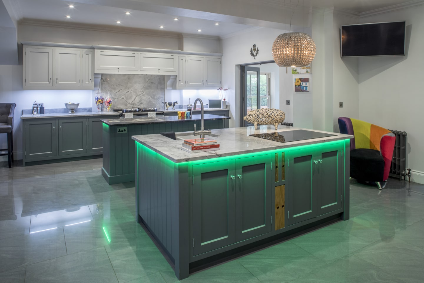 A bespoke kitchen with custom, green LED lighting under the work tops.