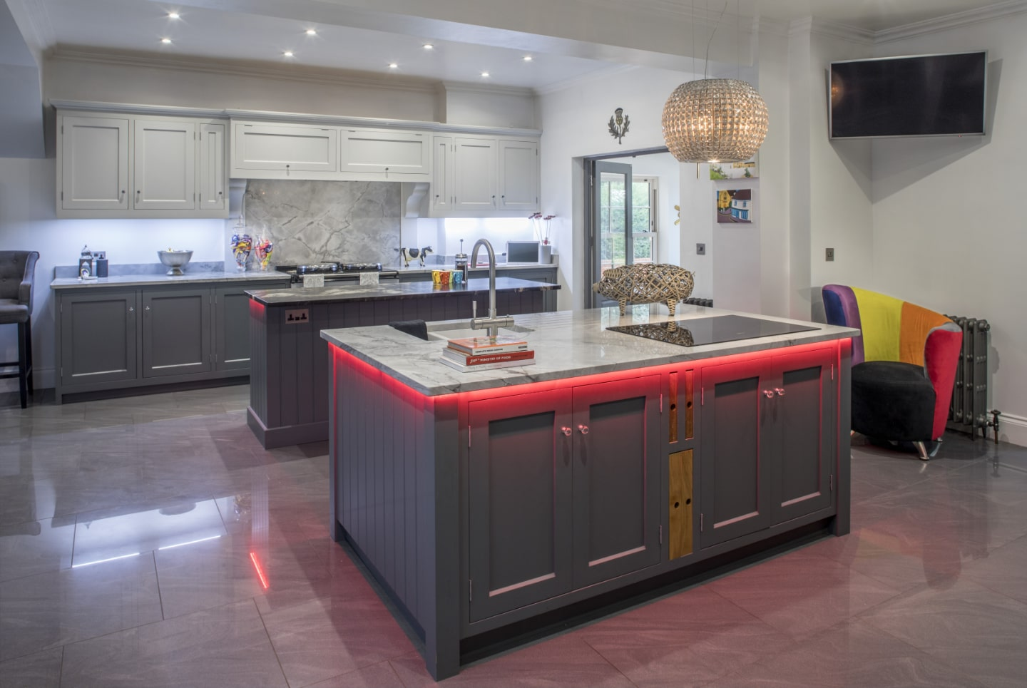 A bespoke kitchen with custom, red LED lighting under the work tops.
