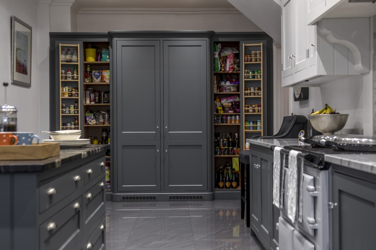 A large pantry with the doors open revealing the food items inside.