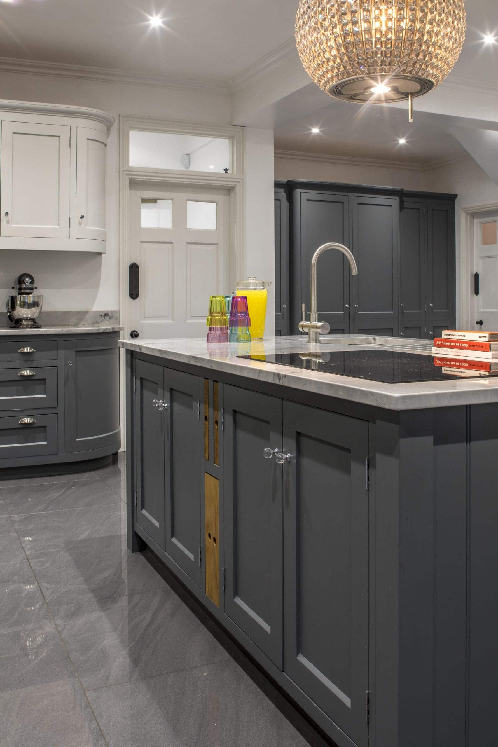A beautiful, bespoke kitchen with a glass light shade