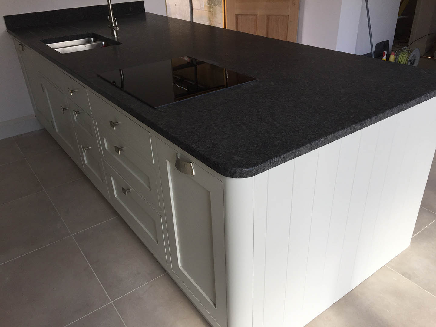 A cooking hob on top of a granite topped surface.