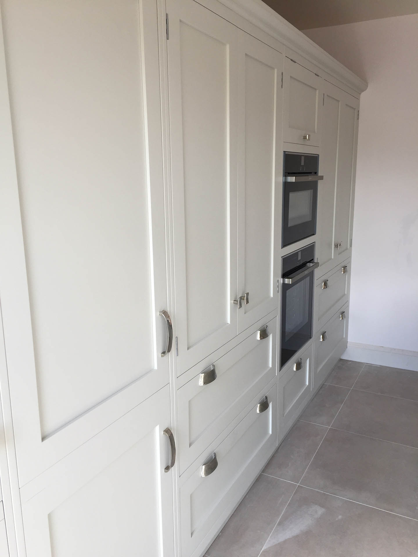 A view of a row of kitchen cupboards with an oven integrated into it.