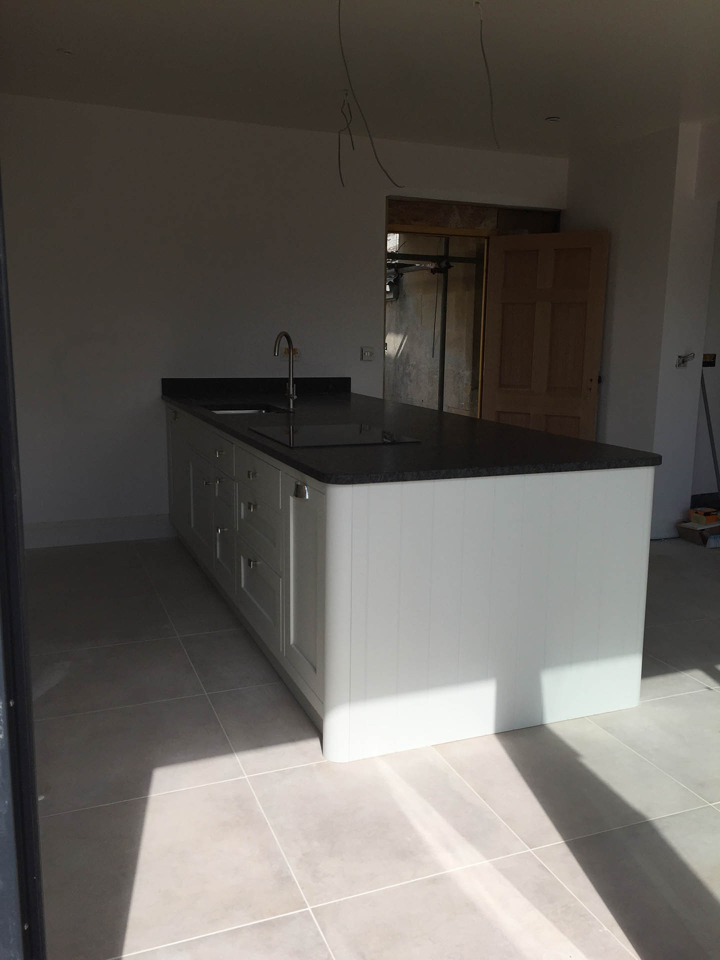 A row of kitchen cupboards with a sink and hob integrated into the surfaces.