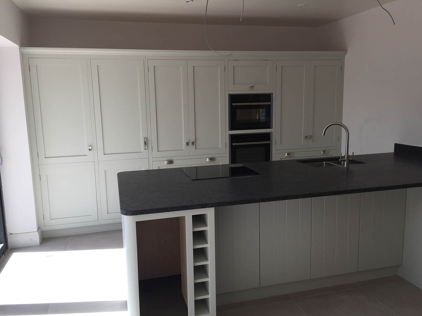 A wide view of a granite topped kitchen