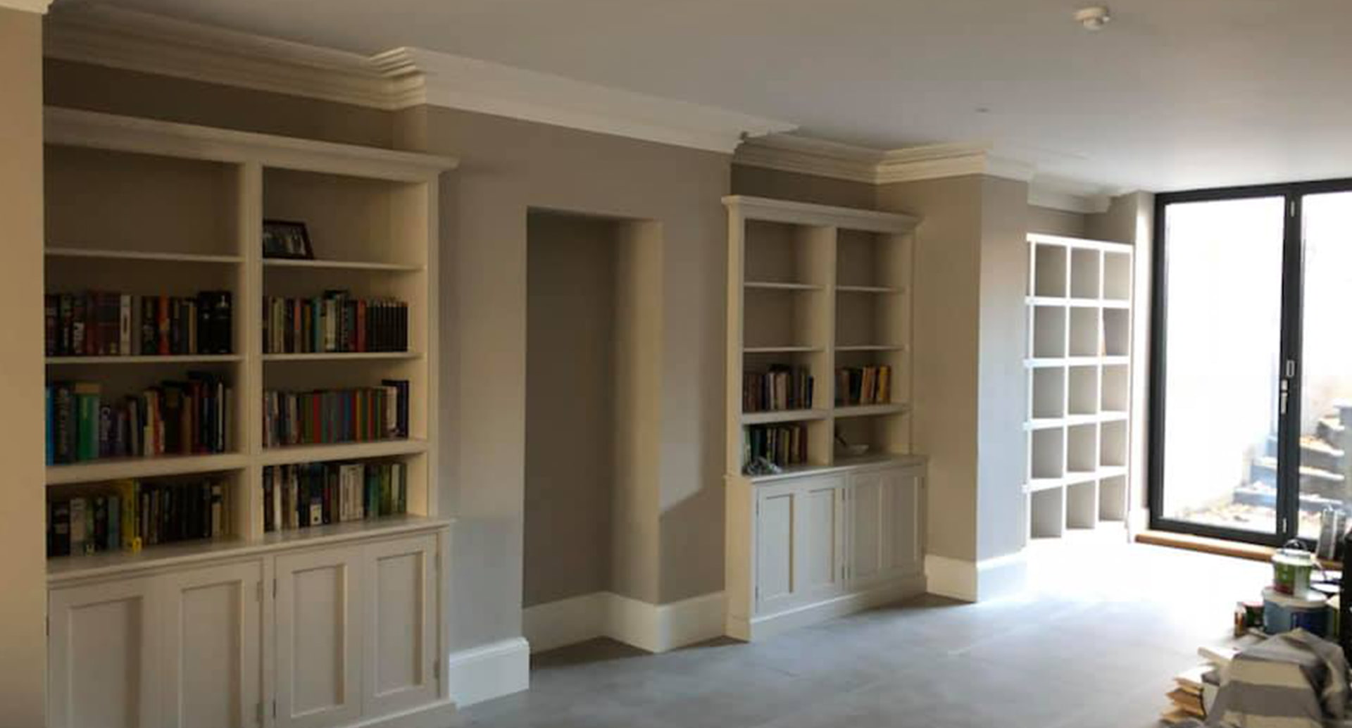 Three, bespoke, book cases with books stacked upon them