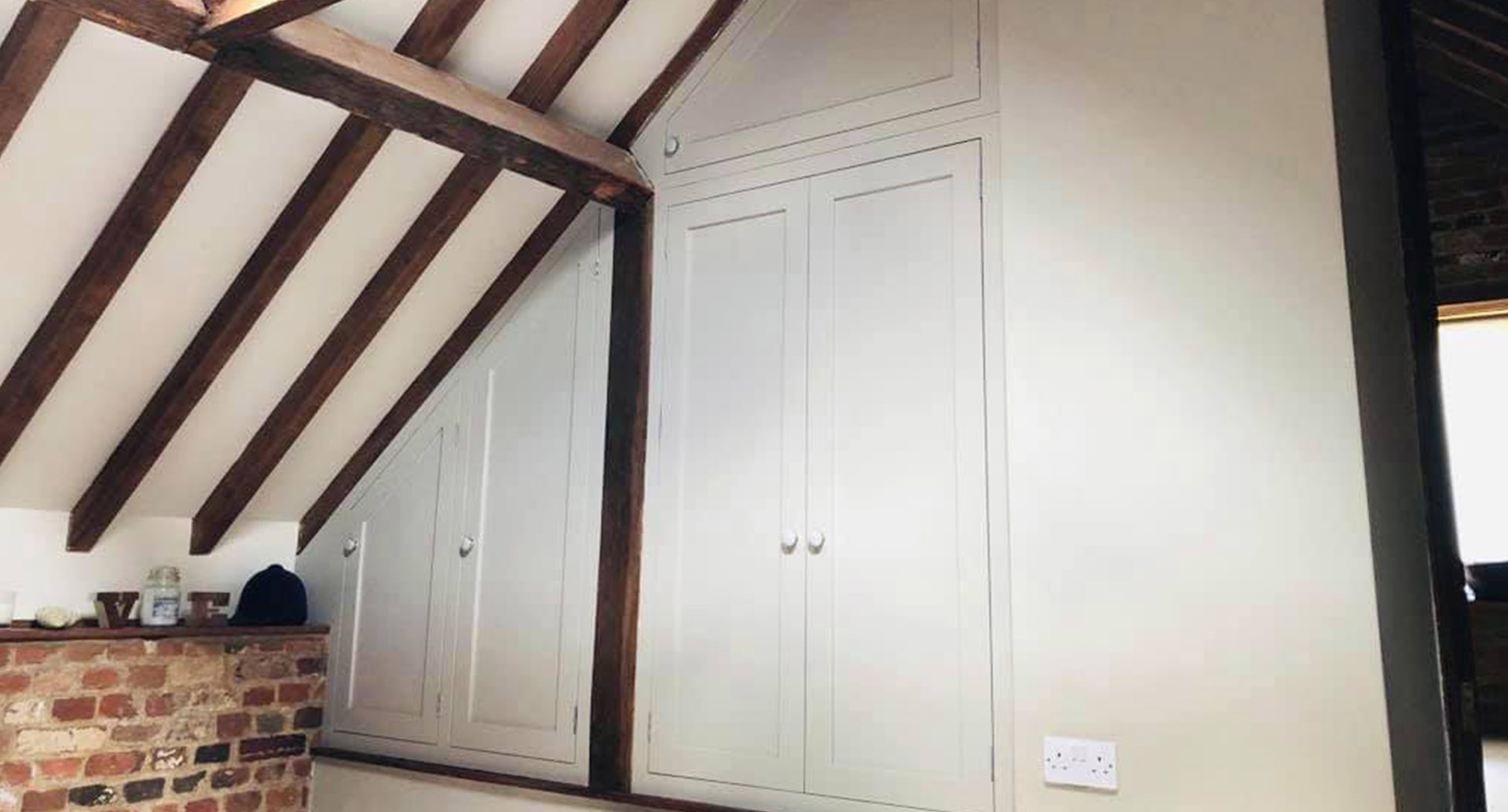 Bespoke wardrobe in attic bedroom with wooden beams