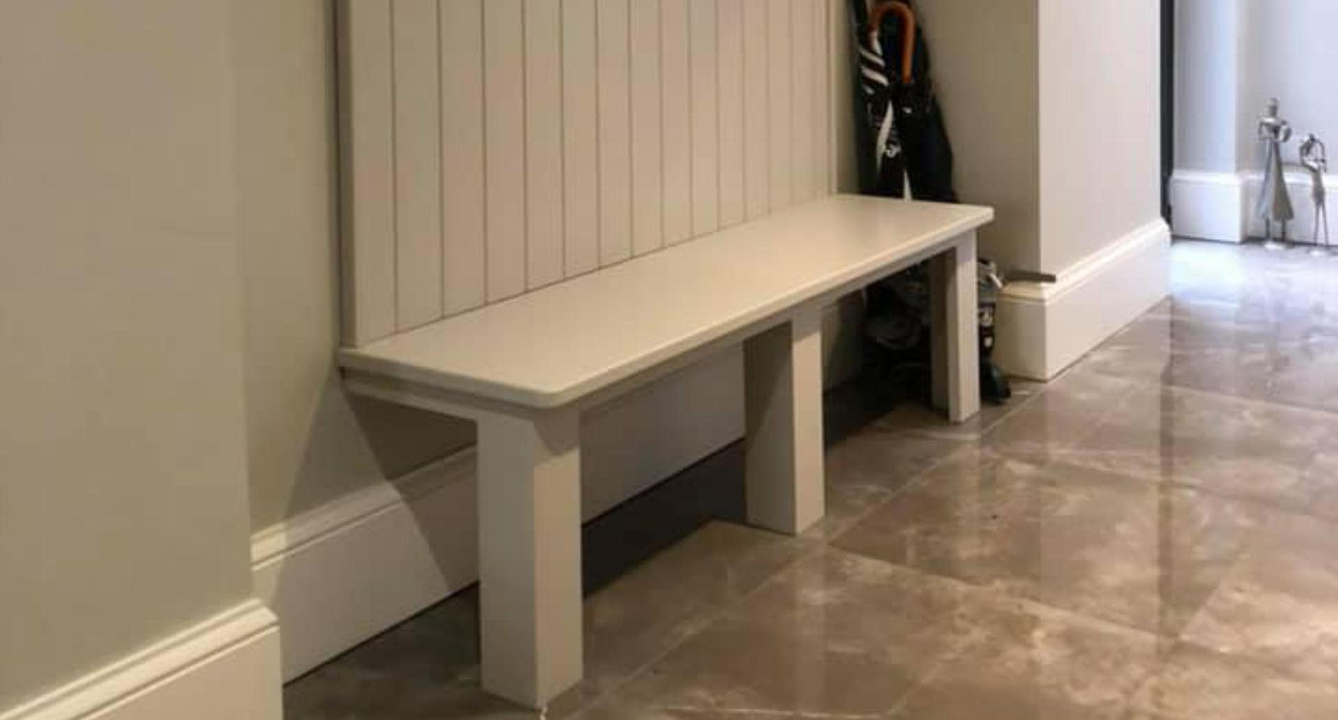 A bespoke, wooden bench with coat hangars in a hallway
