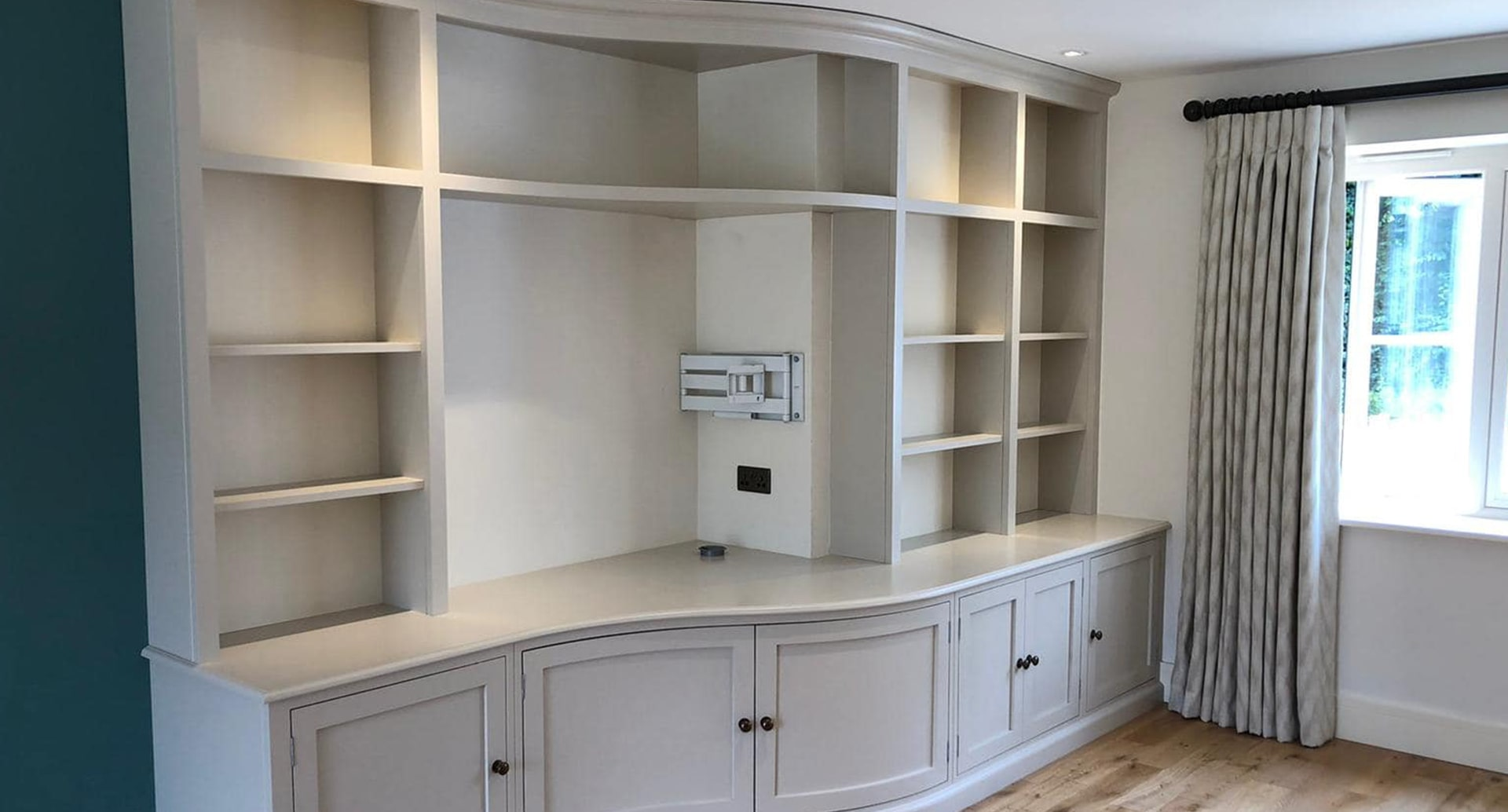A curved book shelf made to fit a wall.