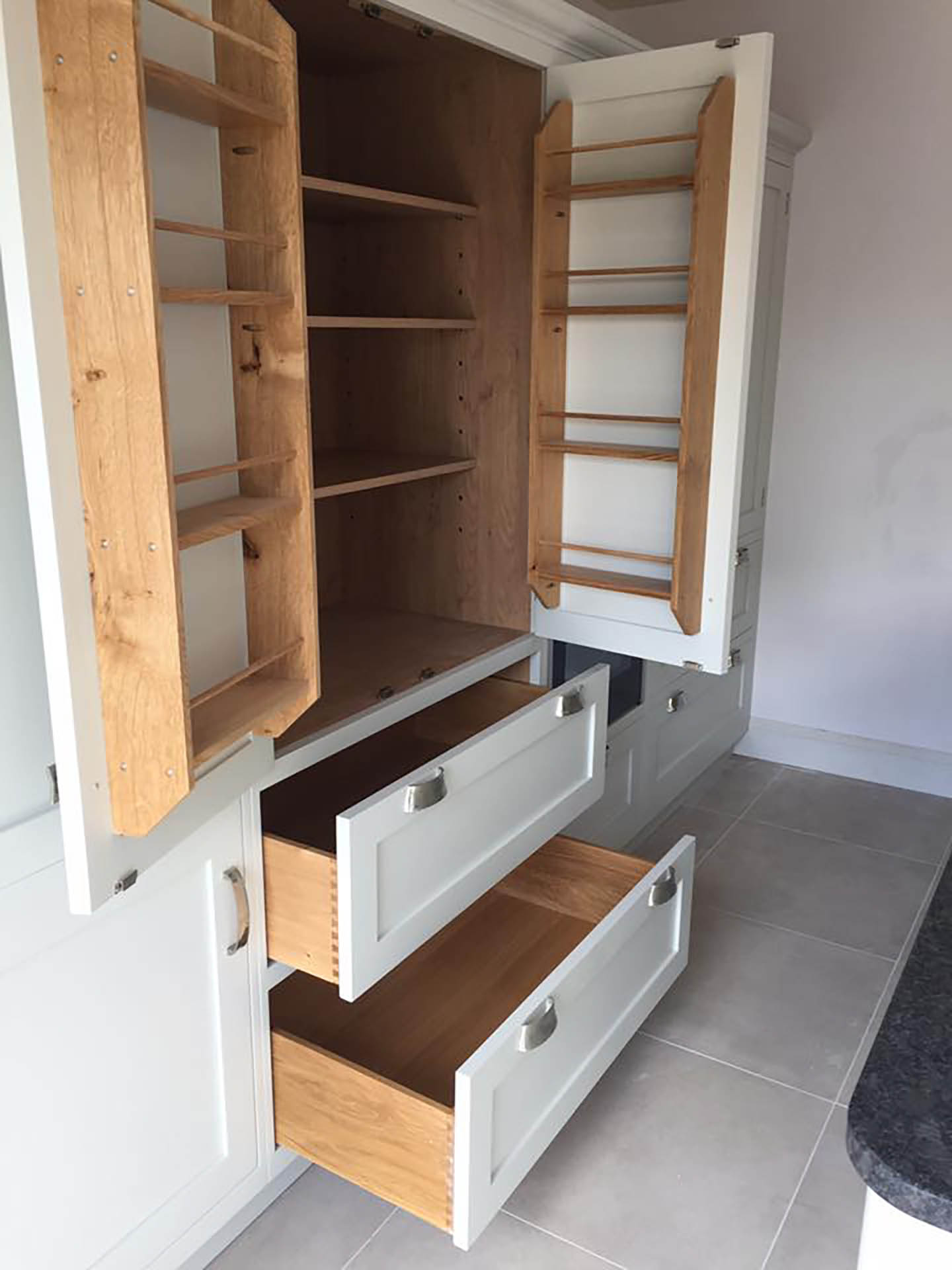 A kitchen pantry which has it's doors and drawers opened