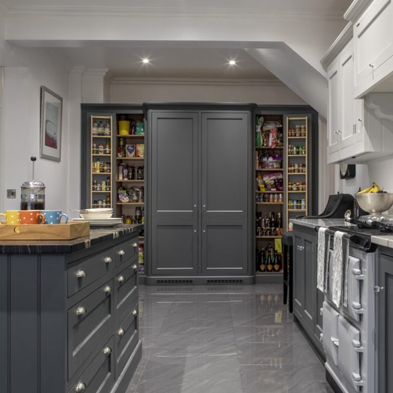A custom built pantry with the doors open to reveal the items inside.