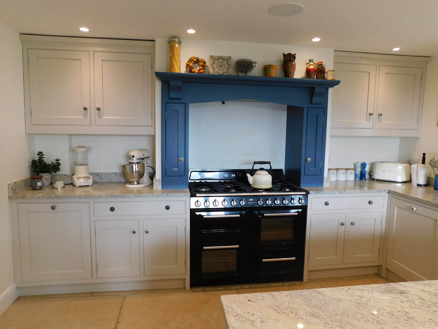 A kitchen cooker hood over a stove with a kettle on one of the hobs.