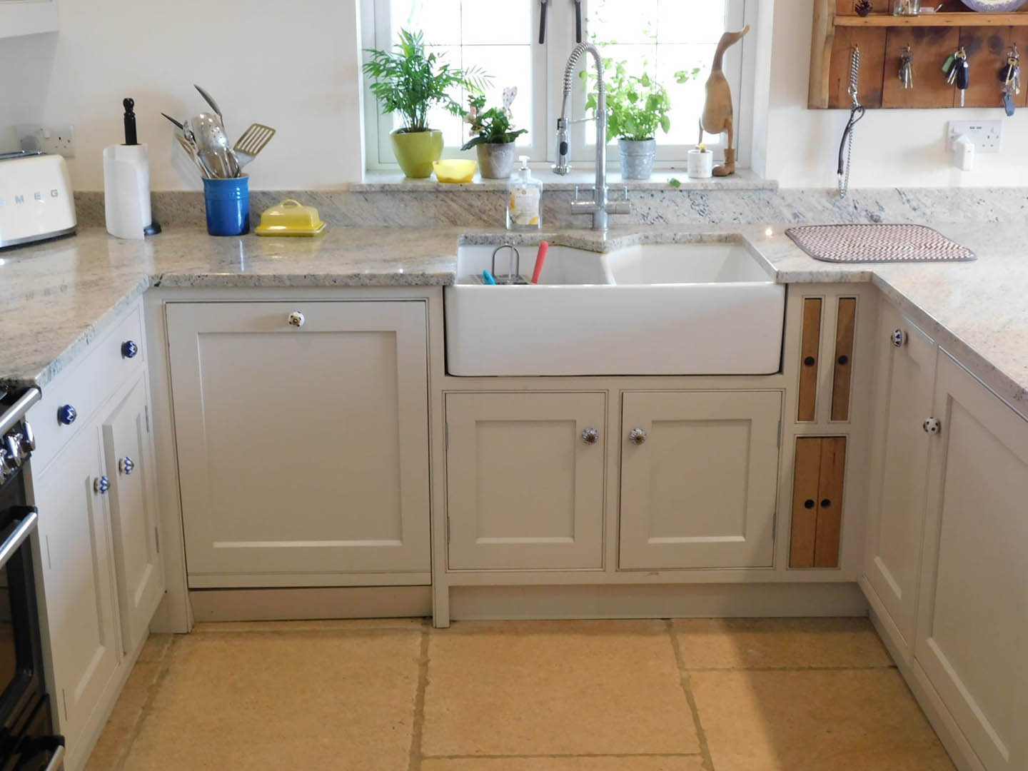 A view of a deep kitchen sink fitted into some marble worktops.