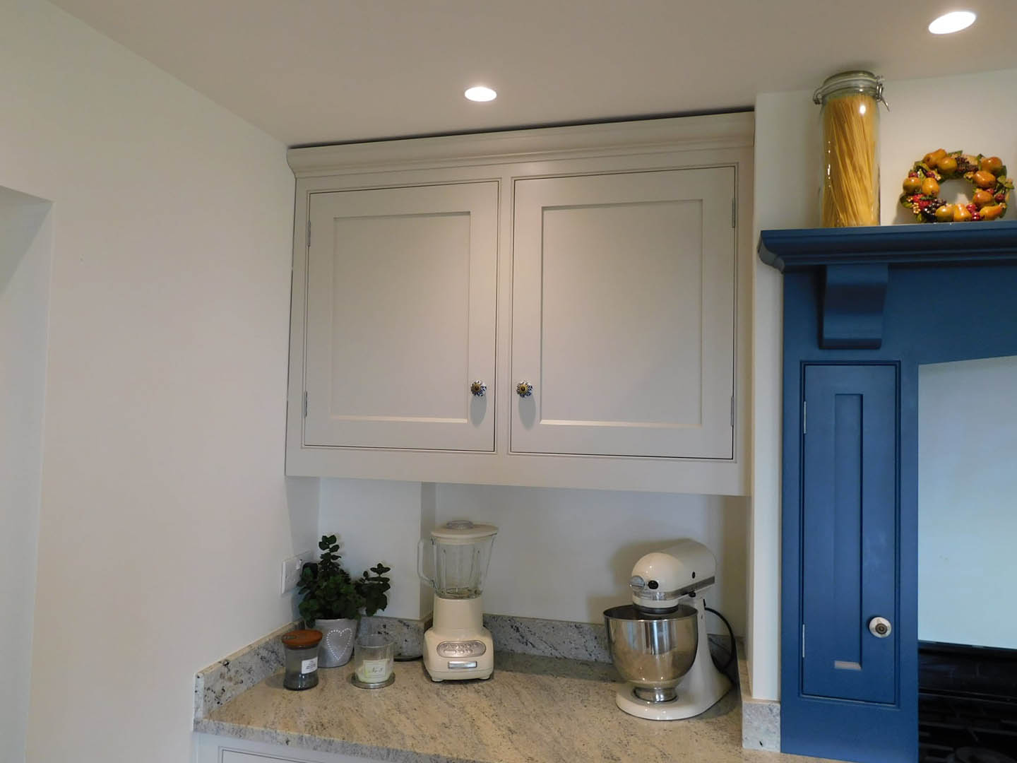 A kitchen cupboard with a mixer and blender beneath it
