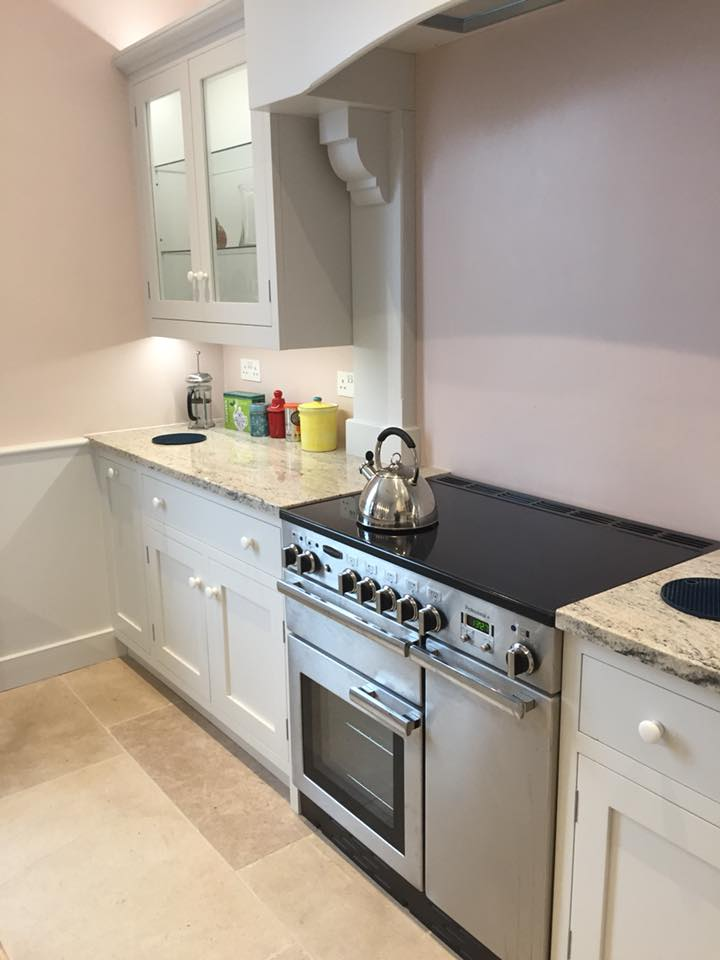 A teapot upon a stove with custom built kitchen cabinets and work tops either side.